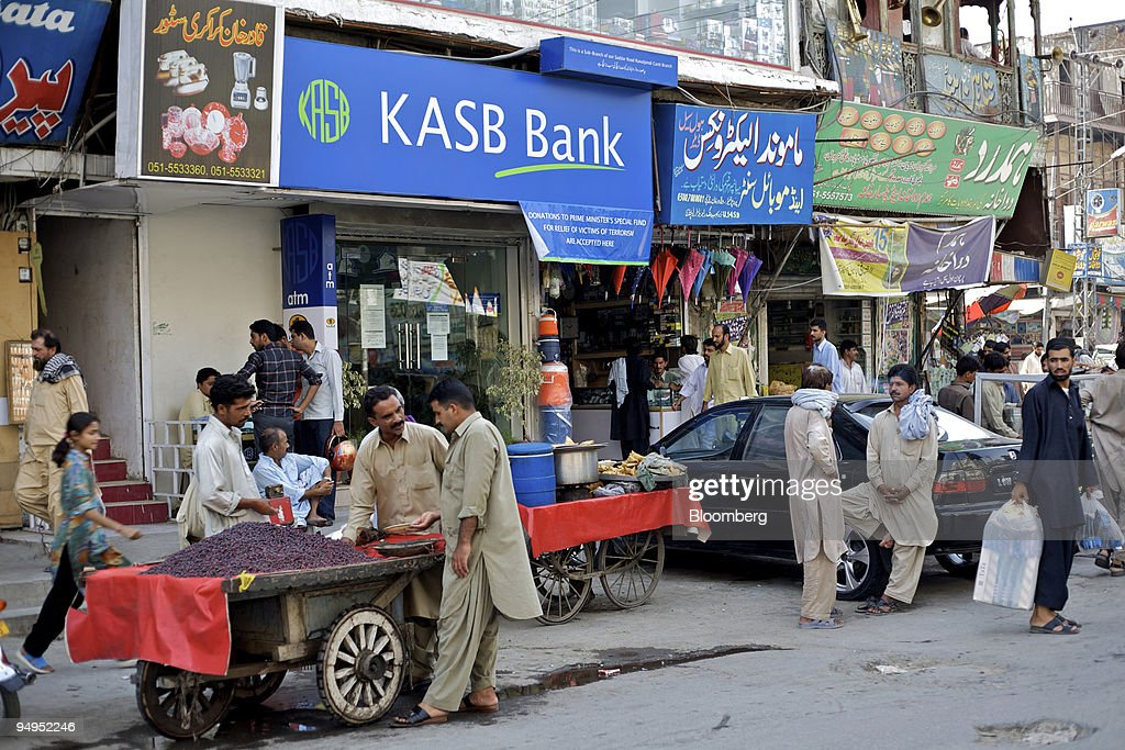 A vendor sells fruit in front of a Khadim Ali Shah Bukhari ( : News Photo