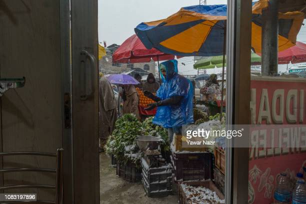 A vendor sells groceries on a roadside amid fresh snowfall on January 16 2019 in Srinagar the summer capital of Indian administered Kashmir India...