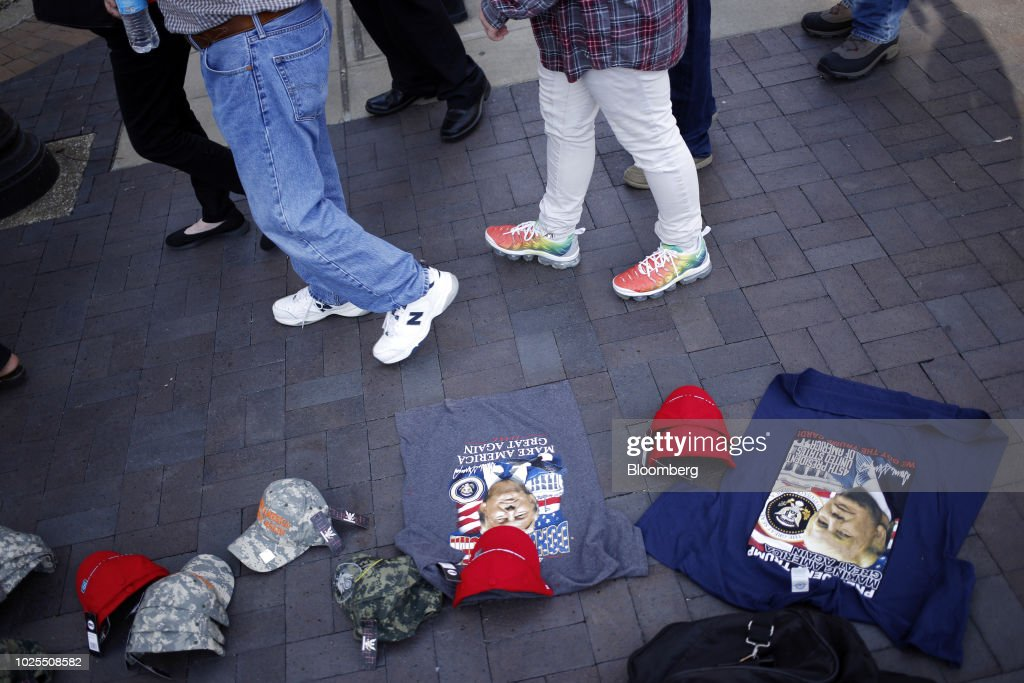 A vendor sells hats and shirts as attendees arrive for a rally with U.S. President Donald Trump in Evansville, Indiana, U.S., on Thursday, Aug. 30, 2018. Trump rejected a European Union offer to scrap tariffs on cars, likening the bloc's trade policies to those of China. Photographer: Luke Sharrett/Bloomberg via Getty Images