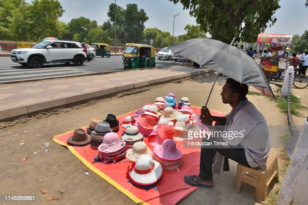 A vendor sells hats on a hot summer day at India Gate on May 21 2019 in New Delhi India Delhi weather has been hot as temperatures continue to settle...