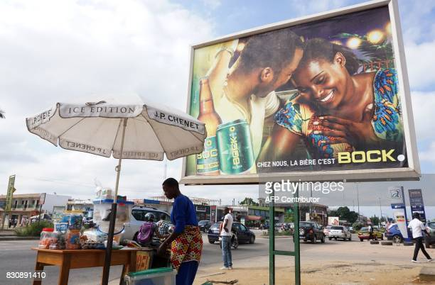 A vendor sells her goods next to a billboard displaying an advertisement for Bock beer in Abidjan on July 13 2017 On posters and huge billboards...