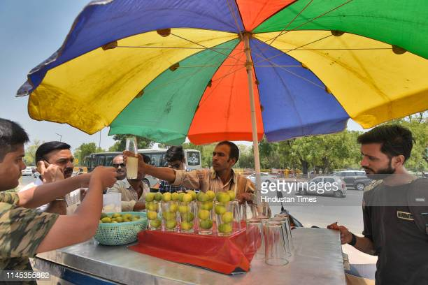A vendor sells isced lemonade or shikanji to customers on a hot summer day at India Gate on May 21 2019 in New Delhi India Delhi weather has been hot...