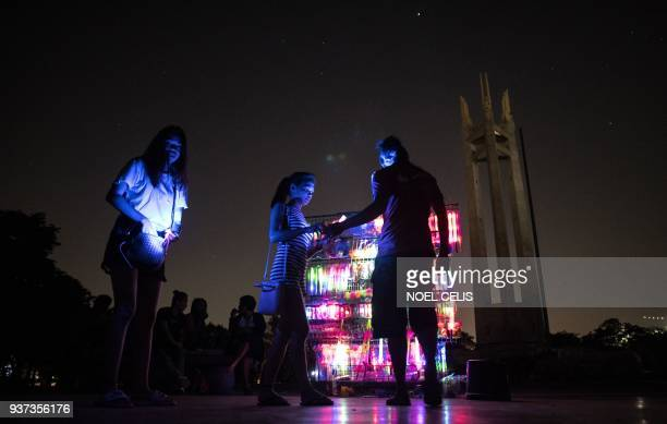TOPSHOT A vendor sells lightup yoys in front of the Quezon Memorial Shrine after the switching off lights for the Earth Hour environmental campaign...
