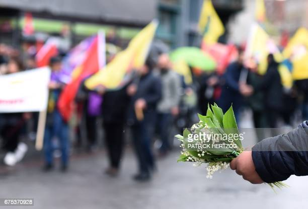 A vendor sells lily of the valley during the traditional May Day rally in Strasbourg eastern France on May 1 2017 / AFP PHOTO / PATRICK HERTZOG