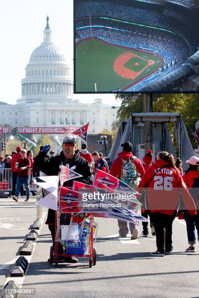 A vendor sells merch as fans gather as the Washington Nationals hold a parade to celebrate their World Series victory over the Houston Astros on...