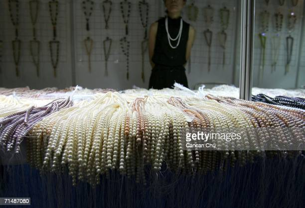 A vendor sells necklaces of pearls at the Beijing International Jewelry Fair on July 20 2006 in Beijing China According to the Gemological...