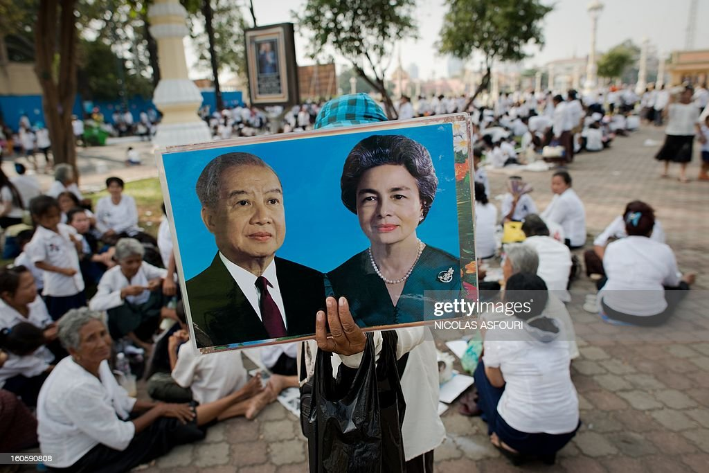 A vendor sells pictures of late former king Norodom Sihanouk and Queen Monique, as Cambodian people come to pray and pay their respect for the late former king Norodom Sihanouk near the Royal Palace in Phnom Penh on February 3, 2013. Thousands of Cambodians have paid their last respects to their beloved former king Norodom Sihanouk as his body lay in state ahead of his cremation on February 4. AFP PHOTO/ Nicolas ASFOURI