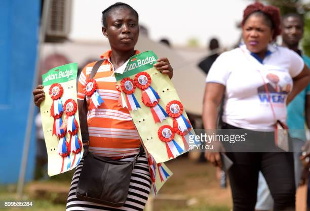 A vendor sells pins with a picture of former football player and winner of Liberia's presidential elections George Weah in front of his party's...