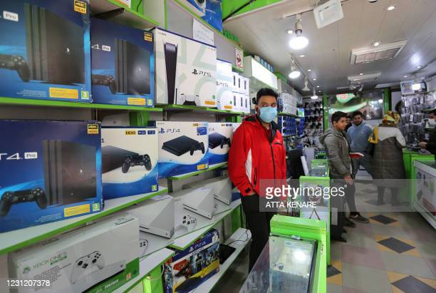 Vendor sells PlayStation 4 , PS5 and Xbox game consoles at a shop in the central market of Iran's capital Tehran on January 24, 2021. - Iran's...