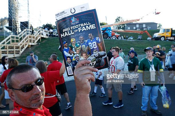 A vendor sells programs as fans of the Green Bay Packers and Indianapolis Colts make their way in prior to the NFL Hall of Fame Game at Tom Benson...