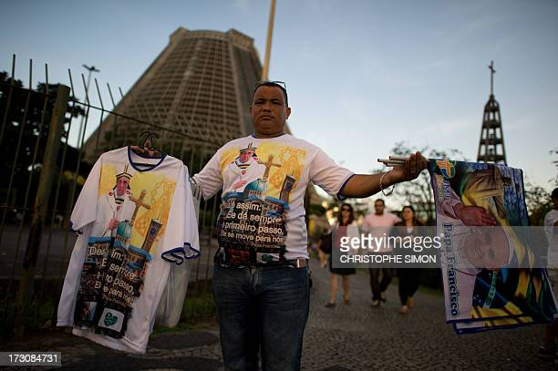 A vendor sells religious souvenirs outside the Metropolitan Cathedral in downtown Rio de Janeiro on July 6 2013 ahead of the upcoming visit of Pope...