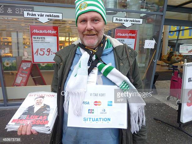 A vendor sells Stockholm's street paper for the homeless wears a sign reading 'we take cards'on October 23 2013 in Stockholm The magazine Situation...