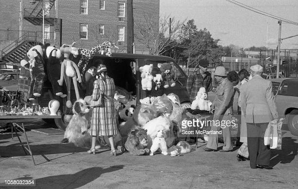 A vendor sells stuffed animals out of the back of a van to passersby in a parking lot in Queens New York New York September 1980