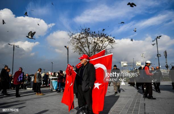 A vendor sells Turkish national flags in Eminonu Square on the European side of Istanbul on January 4 2018 / AFP PHOTO / BULENT KILIC