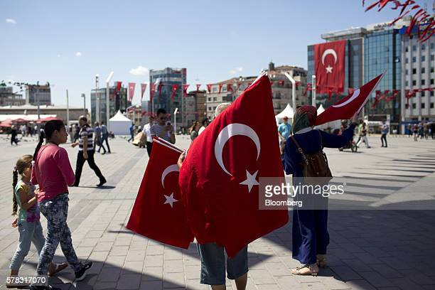 A vendor sells Turkish national flags to pedestrians on Taksim Square in Istanbul Turkey on Thursday July 21 2016 A state of emergency took effect in...