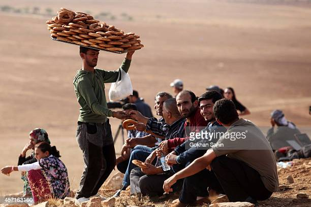 A vendor sells Turkish traditional bagels called 'simit' as people watch the Syrian town of Kobani from near the Mursitpinar border crossing on...