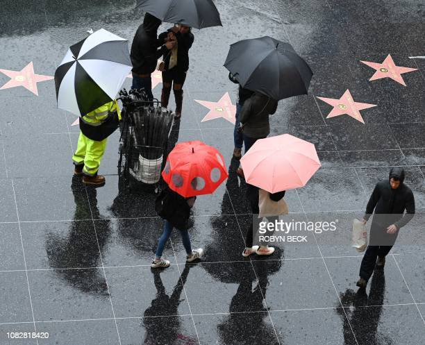 A vendor sells umbrellas in Hollywood California January 14 2019 A storm over Southern California delivered rain and snow heightening the threat of...