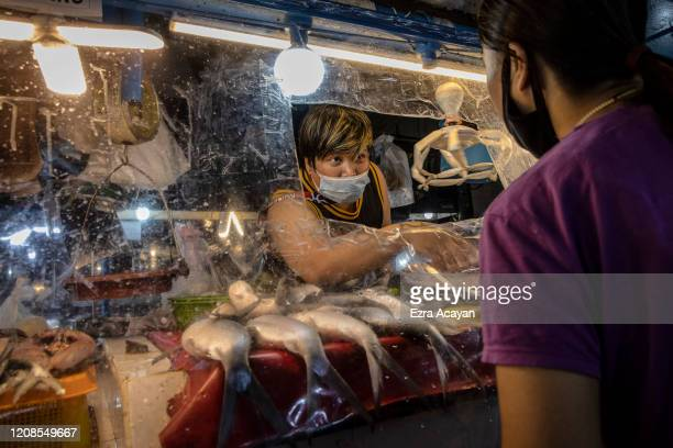 Vendor serves a customer at her stall through a plastic cover to enforce social distancing inside a wet market on March 30, 2020 in Las Pinas, Metro...
