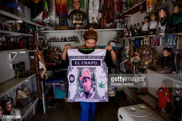 TOPSHOT A vendor shows a shirt depicting a portrait of Mexican drug lord Joaquin El Chapo Guzman at a store next to the narcosaint Jesus Malverde...