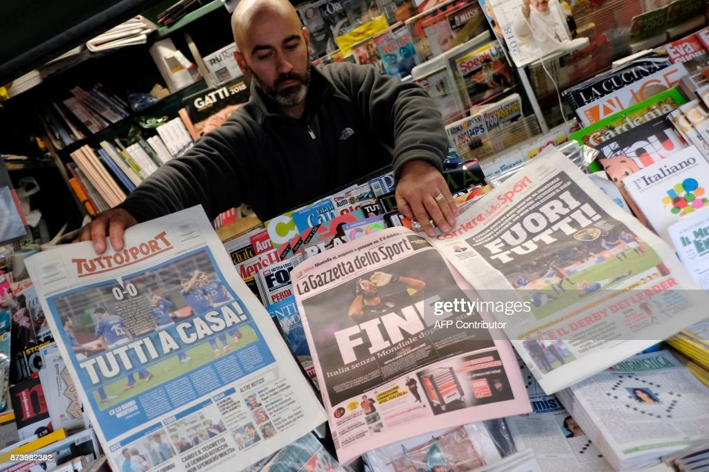 A vendor shows front pages of newspapers a day after the FIFA World Cup 2018 qualification football match between Italy and Sweden, on November 14, 2017 in Rome. Italy failed to reach the World Cup for the first time since 1958 on Monday as they were held to a 0-0 draw in the second leg of their play-off at the San Siro by Sweden, who qualified with a 1-0 aggregate victory. / AFP PHOTO / Andreas SOLARO