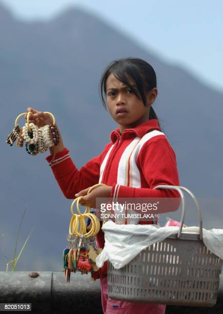 A vendor shows handicrafts to customers at mount Batur tourism area in Kintamani on Bali island on July 24 2008 More holidaymakers heading to...