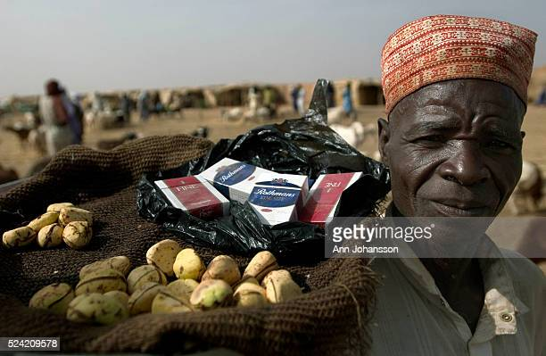 A vendor shows his merchandise for sale at the camel market where livestock is sold in Agadez Niger | Location Agadez Niger