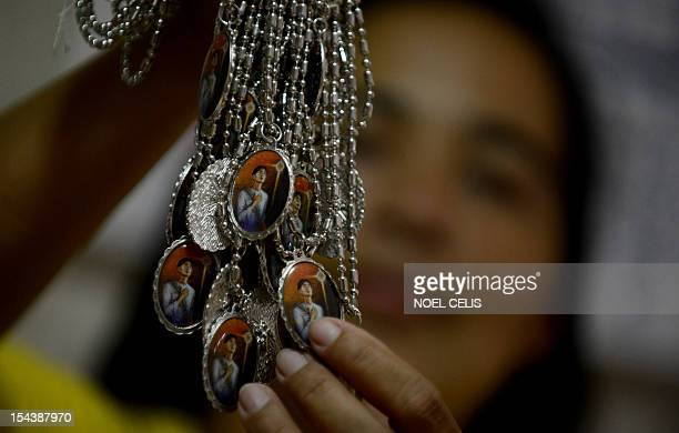 Vendor shows necklaces with a picture of Pedro Calungsod at the Saint Gregory the Great Parish in Cebu on October 19, 2012. Millions of Catholics in...