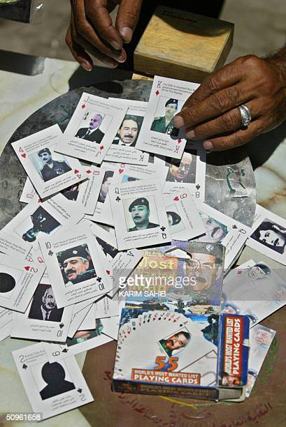 A vendor shows off a pack of cards depicting the 55 most wanted men in Iraq including ousted Iraqi leader Saddam Hussein and his deputies at the Bab...