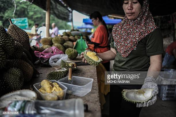A vendor shows the peel of a durian fruit at a roadside shop in Karak in the suburbs of Pahang outside Kuala Lumpur on July 14 2015 The durian...