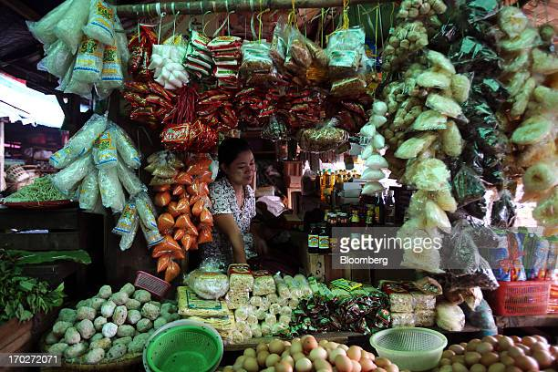 A vendor sits behind condiments and dried noodles displayed for sale at a market stall in Naypyidaw Myanmar on Friday June 7 2013 President Thein...