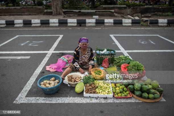Vendor sits in an allocated lot to observe social distancing amid fears over the spread of the COVID-19 coronavirus outbreak as she waits for...