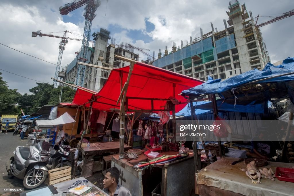 A vendor (C) sits in the shade behind his stall offering fresh meat at a traditional market in Jakarta on February 21, 2018. /