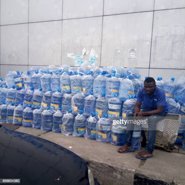 Vendor sits near kegs of water at Apagbon in Lagos Nigeria on Wednesday March 22 2017 Cost of getting quality water in Lagos is rising daily...