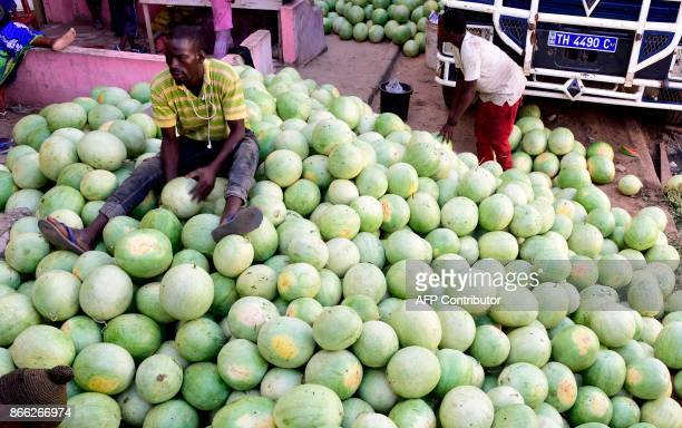 A vendor sits on a pile of water melons at a market in Pikine a suburb of Dakar on October 25 2017 Cultivated in the Senegalese countryside the water...