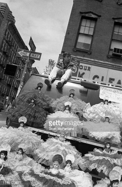 A vendor sits on top of a van behind a stall stocked with dolls in lace dresses on 9th Avenue in Hell's Kitchen New York New York May 14 1988