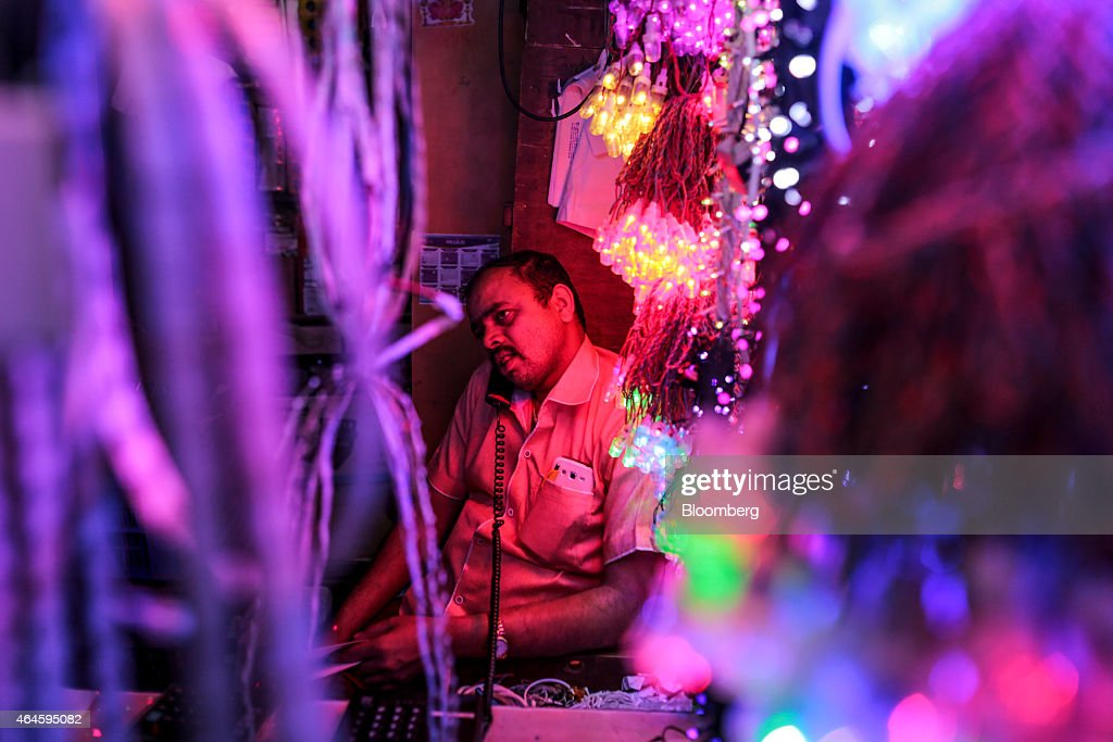 A vendor sits talking on the phone while waiting for customers at a lighting stall in the Null Bazar market area in Mumbai, India, on Thursday, Feb. 26, 2015. India's Finance Minister Arun Jaitley will present this year's budget on February 28. Speculation that Prime Minister Narendra Modi's policies will boost economic growth has propelled India's Sensex to the world's third-biggest gain among major markets during the past 12 months. Photographer: Dhiraj Singh/Bloomberg via Getty Images