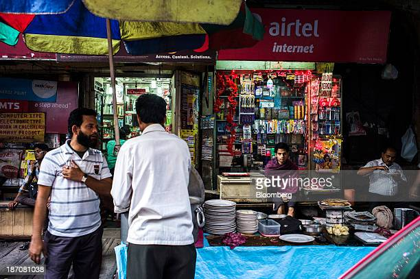 A vendor sits under signage for Bharti Airtel Ltd at a store as a food stall vendor serves a customer in Kolkata West Bengal India on Thursday Oct 31...