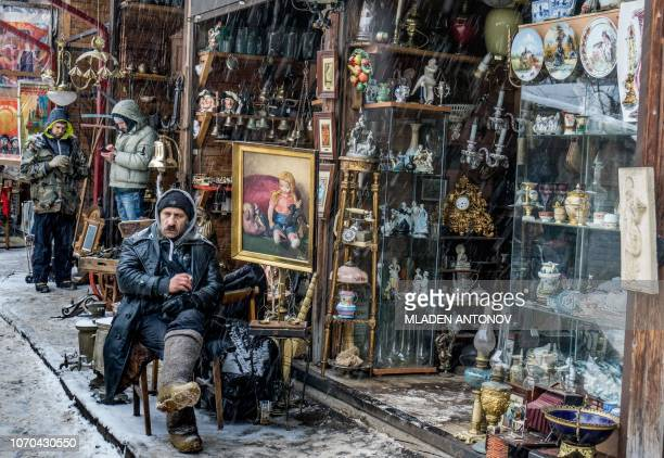 A vendor sits under the snow in front of his shop at Izmailovo flea market in Moscow on December 9 2018