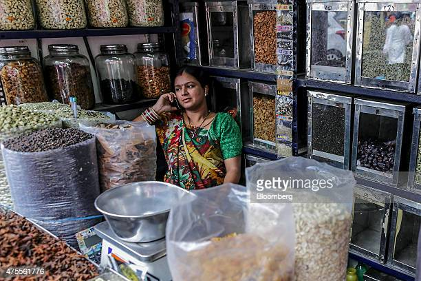 A vendor sits using a mobile phone at a spice store in Ernakulam Kerala India on Thursday May 28 2015 While consumerprice gains eased to a fourmonth...