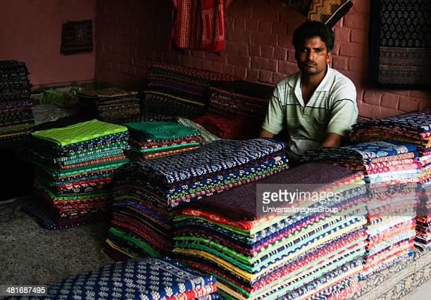 Vendor sitting at a clothing store, New Delhi, India.