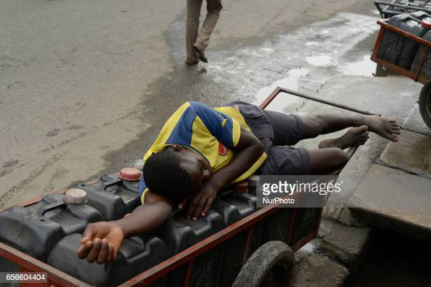 Vendor sleeps on kegs of water at Surulere in Lagos Nigeria on Monday March 20 2017 Cost of getting quality water in Lagos is rising daily Residents...
