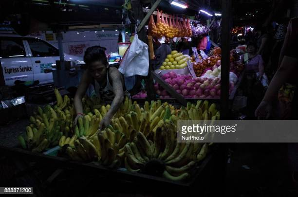 A vendor sorts bananas at a night market along a major highway in suburban Quezon City east of Manila Philippines on Saturday 9 December 2017