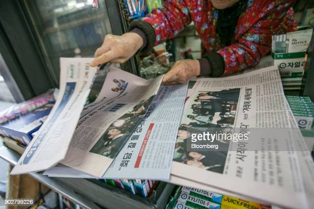 A vendor sorts through newspapers featuring photographs of Cho Myounggyon South Korea's unification minister left shaking hands with Ri Son Gwon...