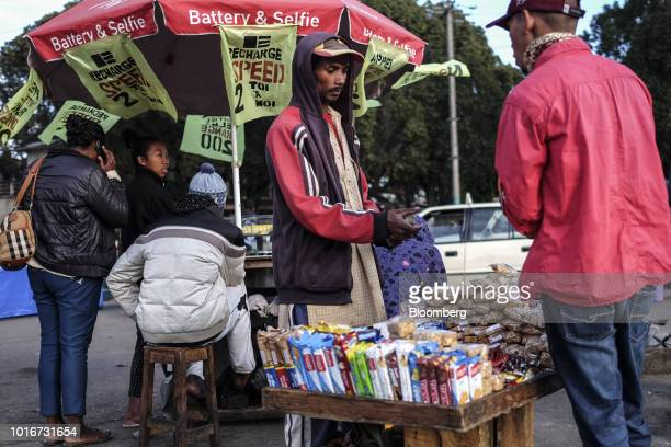 A vendor speaks to a customer at a stall in Analakely Antananarivo Madagascar on Tuesday July 24 2018 Madagascar's gross domestic product figures...