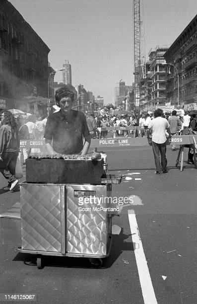 A vendor stands behind a cart on 9th Avenue in Hell's Kitchen during the International Food Festival New York New York May 14 1988