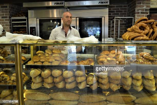 A vendor stands behind bakery goods sitting on a counter at a pastry shop on the third day of Eid alAdha in southern Kahramanmaras province of Turkey...