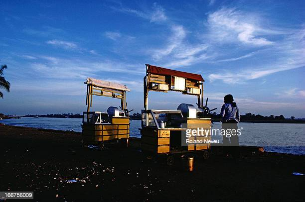 A vendor stands besides her stall along the quiet banks of Mekong river Phnom Penh Cambodia