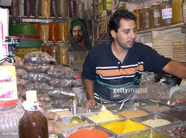 A vendor stands in front of a poster of Shiite Muslim Imam Hussein the son of Imam Ali the cousin of the prophet Mohammed in his spice store in a...
