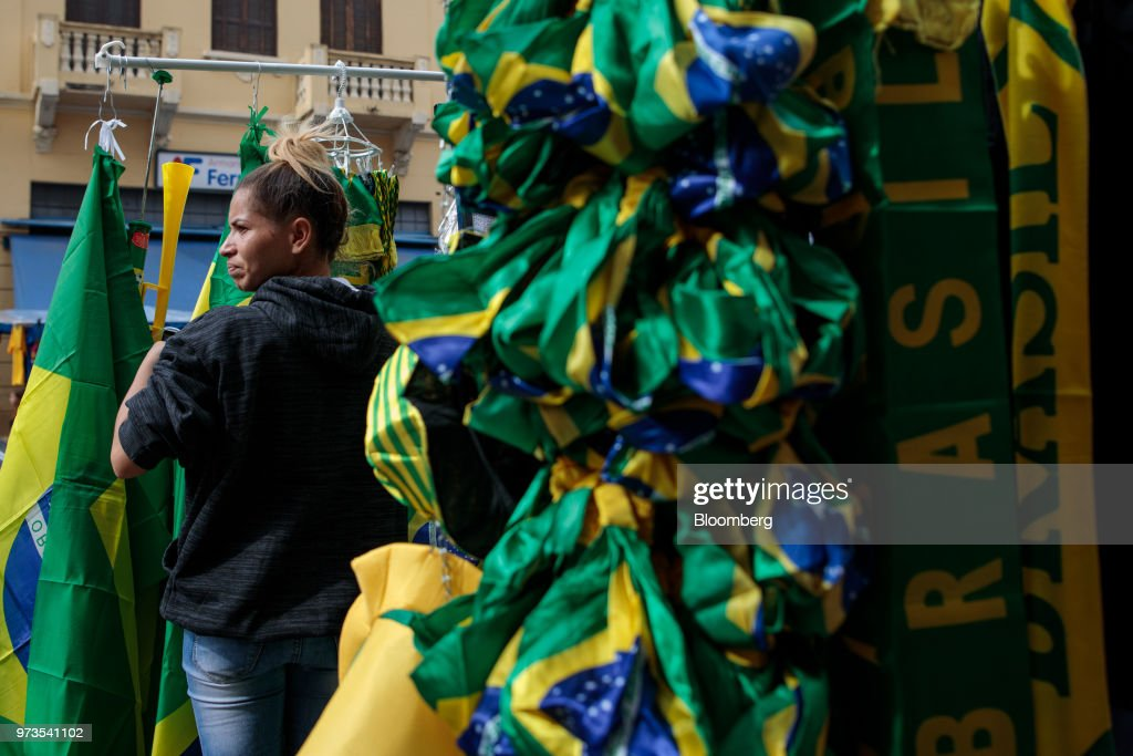 A vendor stands near Brazilian themed objects for sale ahead of the FIFA World Cup games in downtown Sao Paulo, Brazil, on Wednesday, June 13, 2018. In a curious quirk of Brazil's electoral calendar, for the last 28 years Latin America's largest economy has gone to the polls shortly after the World Cup. In the football-obsessed country, politicians have long attempted to hijack the sport to burnish their image. Photographer: Patricia Monteiro/Bloomberg via Getty Images