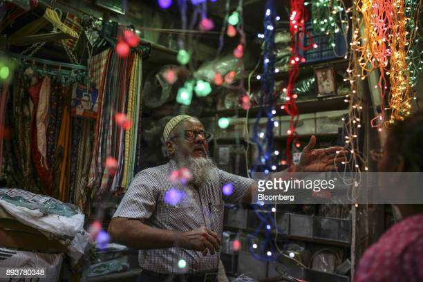 A vendor stands next to festive Christmas lights at a stall in Mumbai India on Friday Dec 15 2017 India's inflation surged past the central bank's...